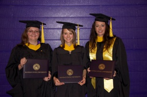 Tiffany Treloar, Hannah Whitcomb, and Kelley Bethell-Smith pose in Bramlage Coliseum after Commencement.